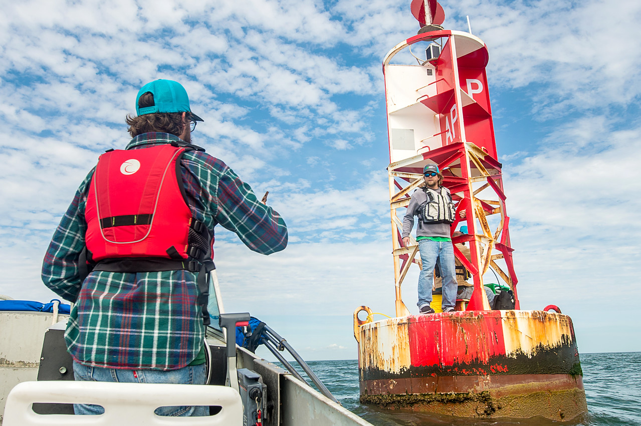 TAMU-CC Conrad Blucher Institute research engineer Hugo Mahlke (left) prepares to hand off a tool to Alistair Lord as he works on a buoy during a CCPORTS module installation off of the coast ...