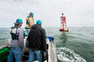 Texas A&M University - Corpus Christi's Conrad Blucher Institute research engineers Alistair Lord (left), Zachary Hasdorff, and Hugo Mahlke arrive at a buoy located a few miles off the coast of Port Aransas, Tx.