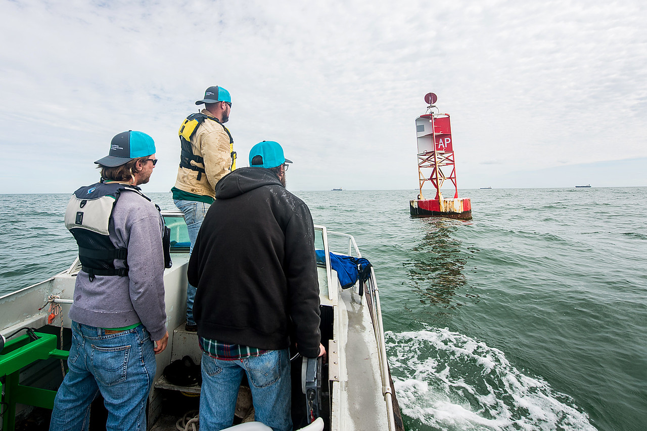 Texas A&M University - Corpus Christi's Conrad Blucher Institute research engineers Alistair Lord (left), Zachary Hasdorff, and Hugo Mahlke arrive at a buoy located a few miles off the coast ...