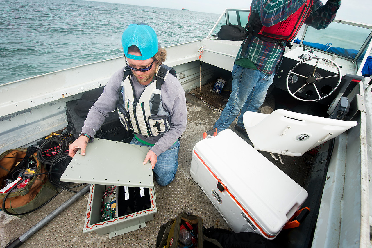 TAMU-CC Conrad Blucher Institute research engineer Alistair Lord places the lid over the box module during a CCPORTS installation off of the coast of Port Aransas, Tx.