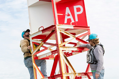 TAMU-CC Conrad Blucher Institute research engineers Zachary Hasdorff (left), and Alistair Lord work on a buoy during a CCPORTS module installation off of the coast of Port Aransas, Tx.