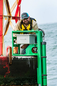 TAMU-CC Conrad Blucher Institute research engineer Zachary Hasdorff installs a module to the buoy during their CCPORTS installation off of the coast of Port Aransas, Tx.