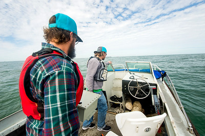 TAMU-CC Conrad Blucher Institute research engineers Hugo Mahlke (left), and Alistair Lord  move a module towards the front of the boat; during their installation of the CCPORTS system off of the Port Aransas, Tx coast.
