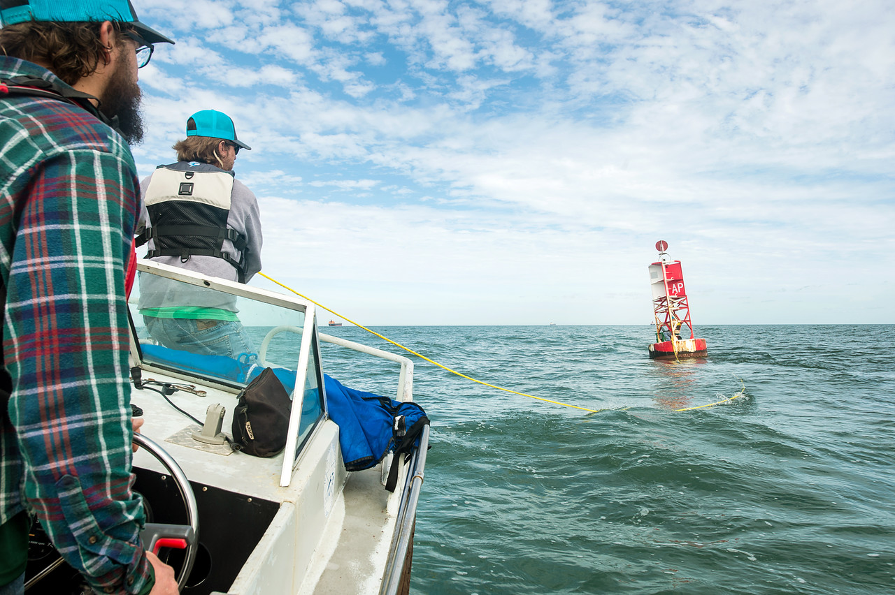Hugo Mahlke (left) and Alistair Lord, research engineers from the university's Conrad Blucher Institute for Surveying & Science, pull on a rope to spin a buoy as they calibrate the CCPORTS s ...