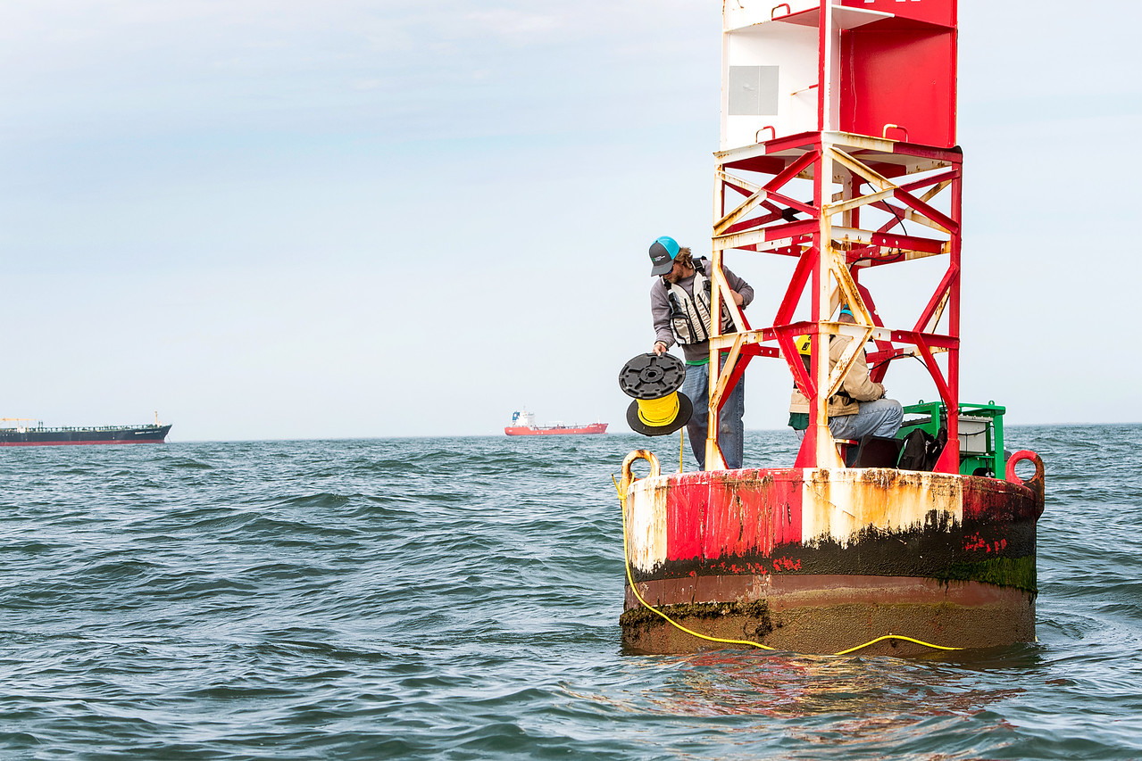 TAMU-CC Conrad Blucher Institute research engineers Alistair Lord (left), and Zachary Hasdorff wrap a rope around a buoy during a CCPORTS module installation off of the coast of Port Aransas ...