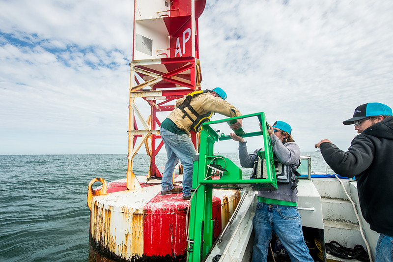 Zachary Hasdorff (left), Alistair Lord, and Hugo Mahlke, work together to move the clamperatus off of the ship and onto the buoy as they install a CCPORTS system.