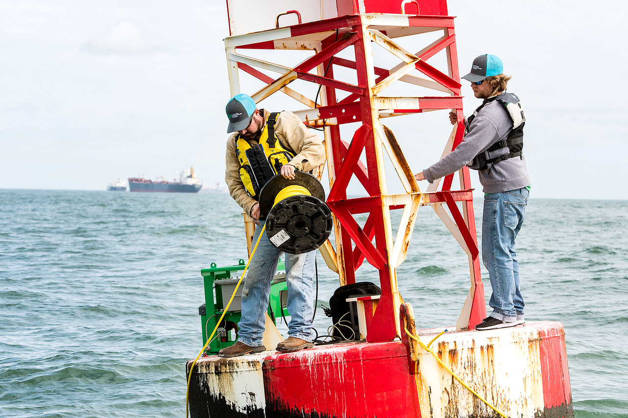 TAMU-CC Conrad Blucher Institute research engineers Zachary Hasdorff(left), and Alistair Lord wrap a rope around a buoy during a CCPORTS module installation off of the coast of Port Aransas, ...