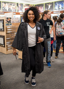 Clarice Reece shows her Islander Pride while finding the right graduation gown during the Islander Grad Fair in the University Center Barnes and Noble.
