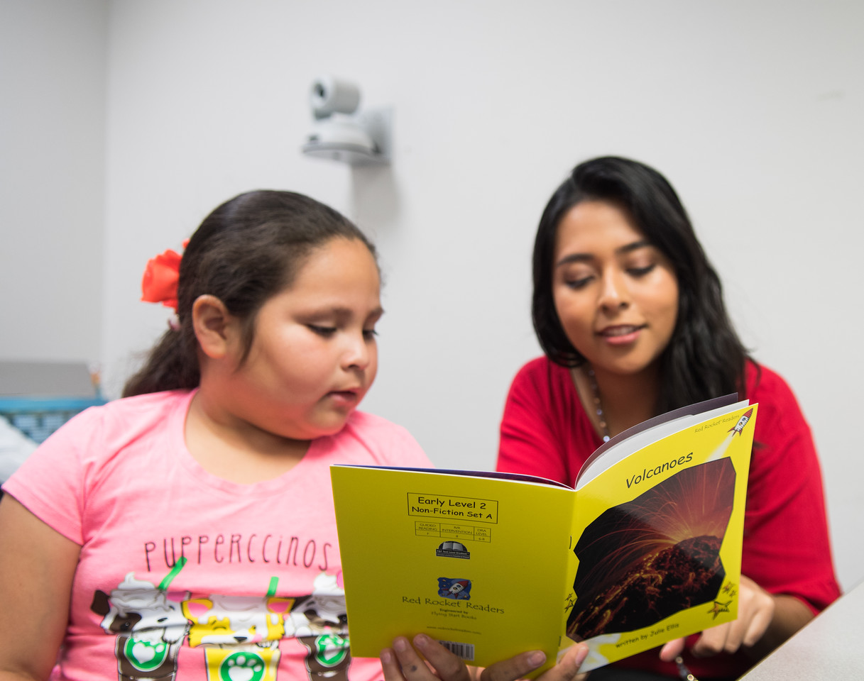 "Karligth Flurs (right) reads Red Rocket Readers ""Volcanoes"" to Marijo Acosta"