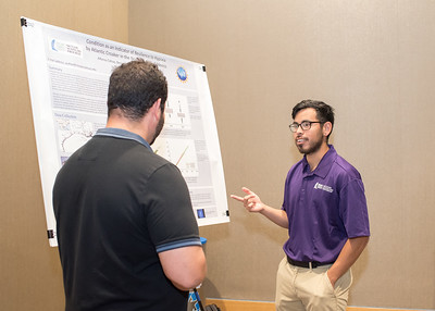McNair Scholar Alfonso Cohuo (right) explains his poster presentation to another student.