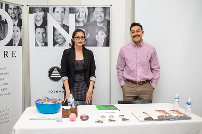 Waddell & Reed representatives Laura Villarreal (left), and Ben Lopez provide information for jobs and internships during the College of Business' Career Fair in the O'Connor building.