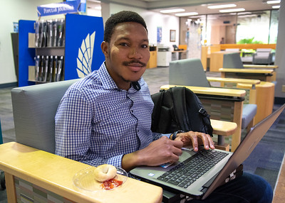 Kehinde Agbaje enjoys bagels at the mAry and Jeff Bell Library as he studies for finals