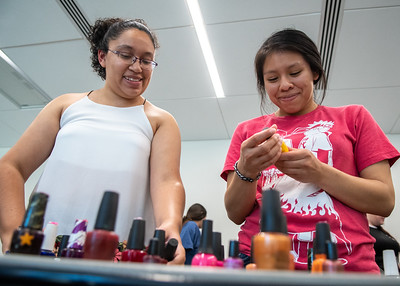 "Dulce Garcia (left) and Andrea Coj get ready to choose a color as their next to get their nails painted for ""Treat Yourself"" event during finals week at the University Center"