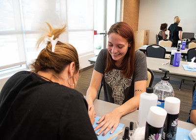 "Natasha Ryan (right) has a great time while getting her nails painted by Kelly Garcia during finals week at ""Treat Yourself"" event at the University Center"