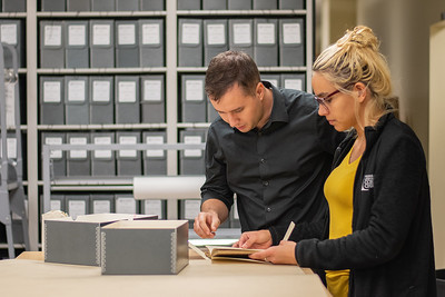 SQL Coordinator Bryan Gillis (left), and Library Specialist II Shelby Gonzalez examine archived journals in the Mary and Jeff Bell Library collections.