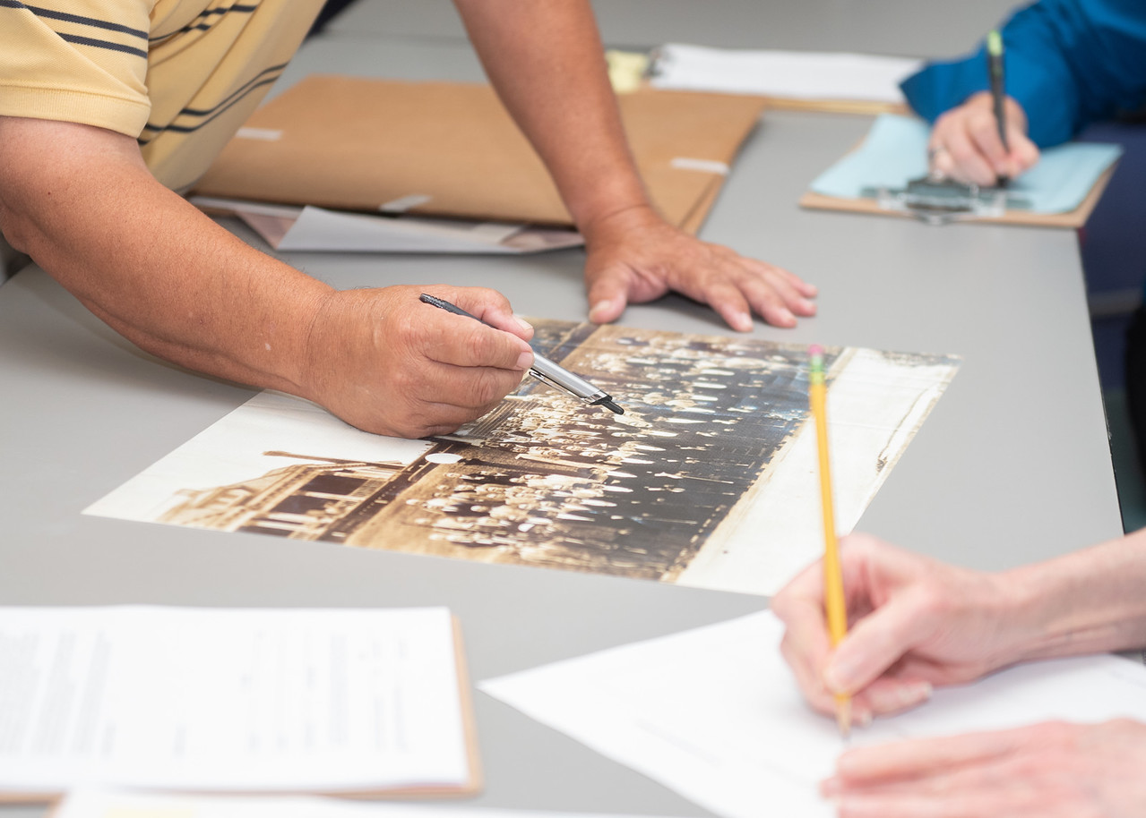 Alfonso Gomez donates historical photos to be archived by the staff of the Mary and Jeff Bell Library during the Public History Harvest.