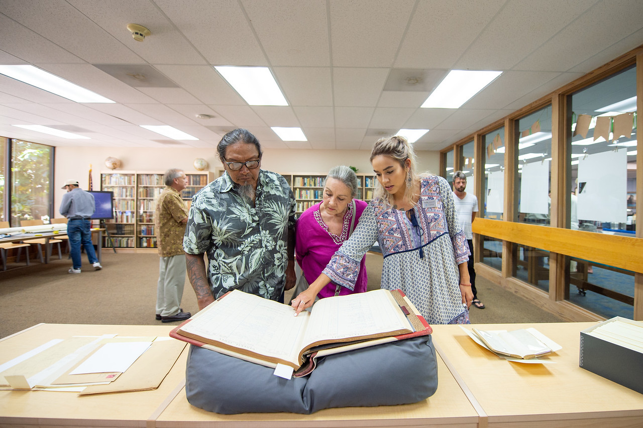 Henry Gonzalez (left), Sandra Jerabek, and Shelby Gonzalez look through a general indez from 1943.