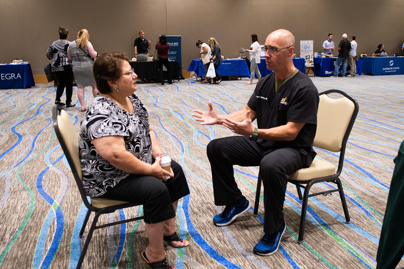 John Shireman (right) sits down with Linda Villarreal to discuss sports medicine therpay at the open enrollment benefits fair at the UC anchor ballroom