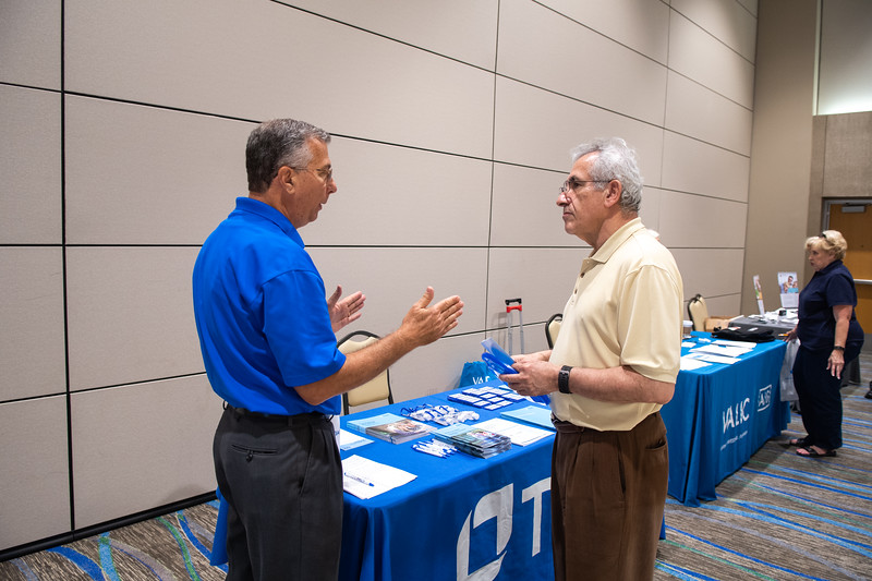 Amir Hormozi (right) stops by the TIAA table to get some information from vendor Charles Downing