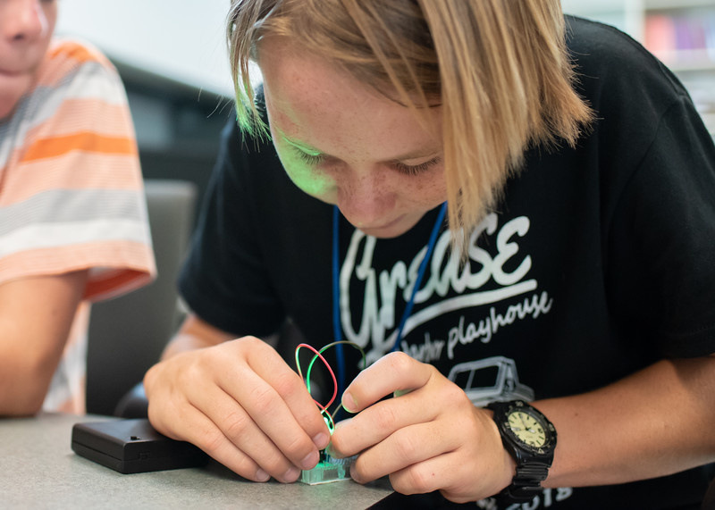 Camper Kai Meyer works with electrical wires in order to produce a light during the STEM Summer Camp.