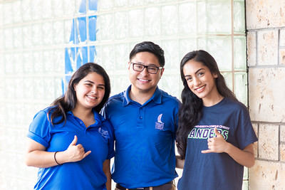 Idania Garza (left), Rene Zamora, and Anuja Dhakal set up outside the Welcome Center to assist students on their first day of classes.