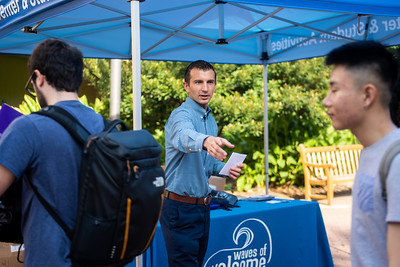 Travis Whipple hands out Waves of Welcome bags filled with free food and giveaways to help get students off to a good start for the fall semester.
