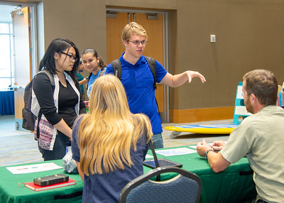 Tiara Sison (left) and Henry Elicker talk to representatives from Texas Parks and Wildlife during the Corpus Christi Community Fair.