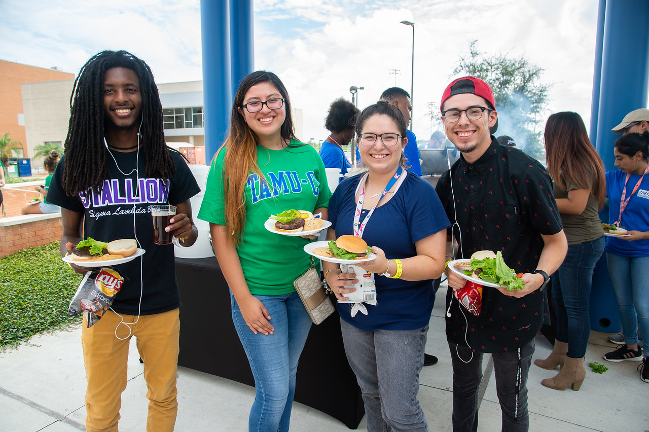 Christopher Tucker (left), Ashley Ventura, Valerie Luniz, and Juan Reyes stop by the All American Red, White and Blue cookout for some burgers at the University Center Sea Breeze Patio.