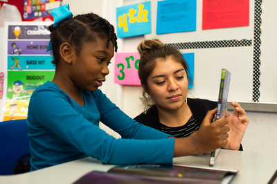 """Teacher candidate Maria Anaya assists student Harmony Clemmons on discussing the summary of """"Ghosts in the House""""."""