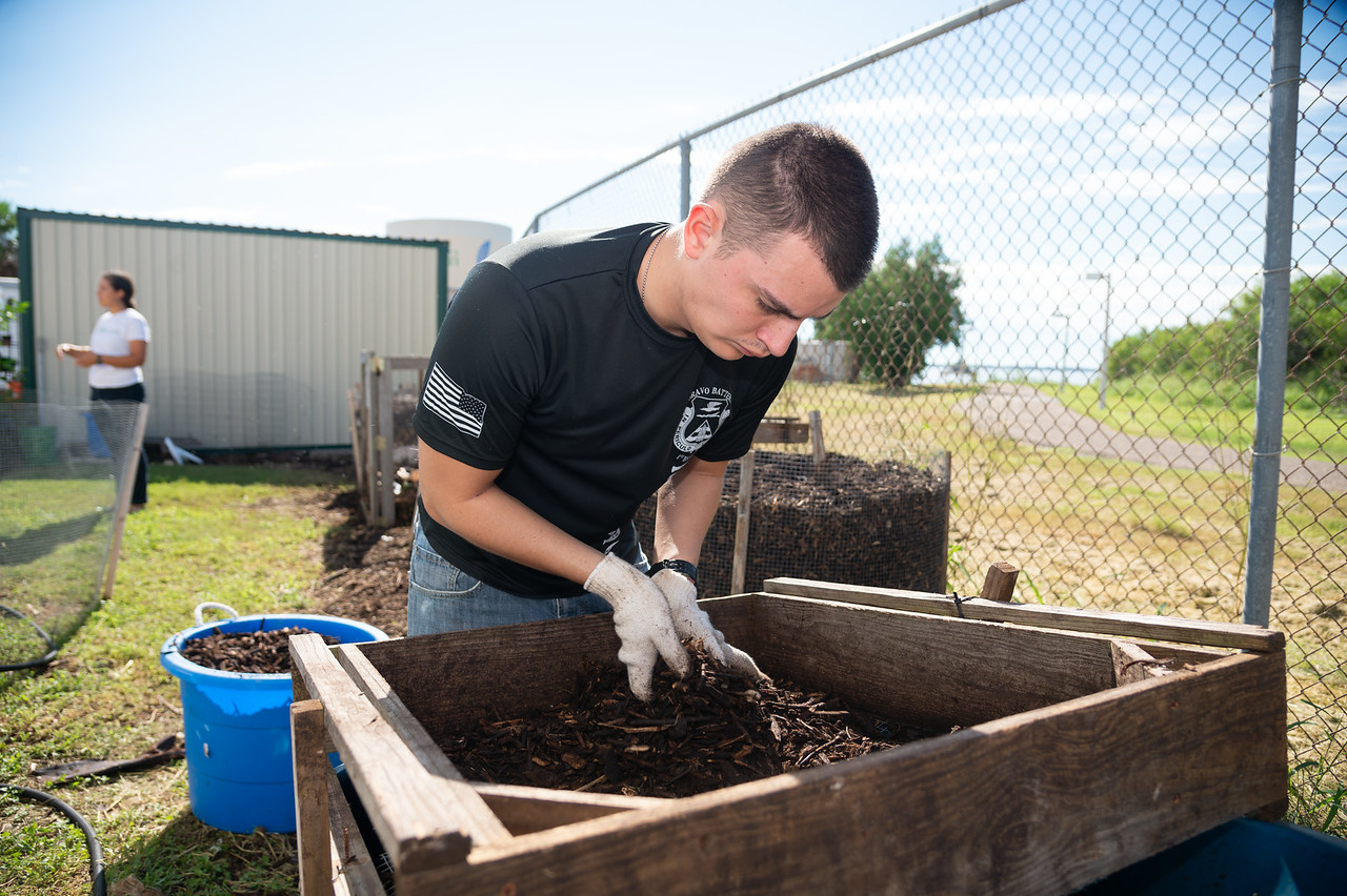 Student, Mark Rolph volunteers at the Islander Green Garden by assisting with the compost process.
