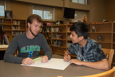Garrett Swenson (left) with a West Oso High School student at the Spanish event at the library.