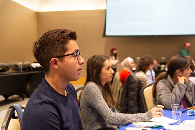 Jonathan Flores (left) listens to the international speakers.