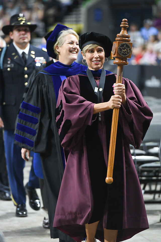 Dr. Corinne Valadez, Associate Professor of Education, Silverman Endowed Professor in Literacy, and recipient of the University Excellence Award in Service, carries the ceremonial mace durin ...
