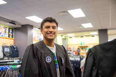 Austen Serrata finds the right size gown for his upcoming graduation.