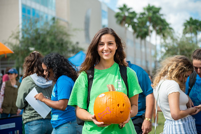 Freshman psychology student Savannah Walker poses with her carved pumpkin at the Fall Festival.