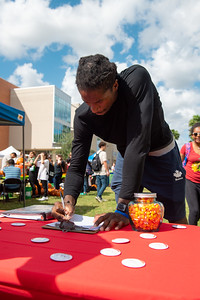 Communications major Irshaad Hunte gives his best guess for the amount of candy corns are in the jar at the Fall Festival.