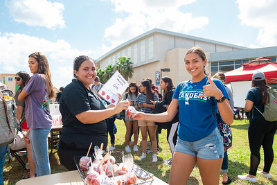 Dining Staff member Ashley Cisneros (left) gives out free candy apples to students, including nursing student Kayla Salinas.