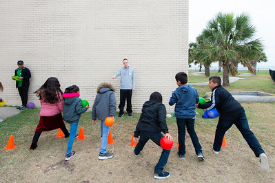 Brandon Linhart gives instruction to elementary students on how to receive a ball after it bounces.