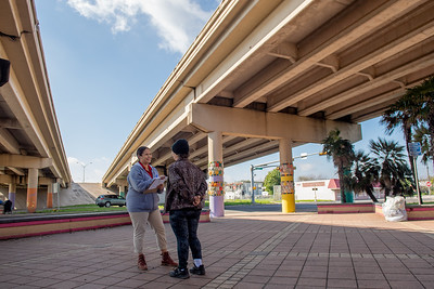 Amber Rosales (left) interviews Royanne Diffley as surveys are taken at the Crosstown Expressway underpass.