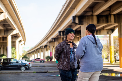 Amber Rosales (right) interviews Royanne Diffley as surveys are taken at the Crosstown Expressway underpass.