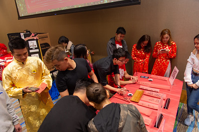 Students gather around the calligraphy table to write out Chinese words.