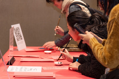 Students perform calligraphy using traditional Chinese symbols.