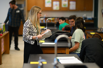 Aquatic Science teacher Shelby Szteiter provides paper to students for a project.