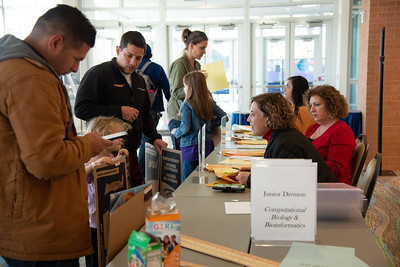 Volunteers help students and their parents check in for the science fair.