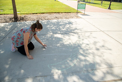 Campus Activity Member, Angelina Tapia creates a chalk art ad in Anchor Plaza.