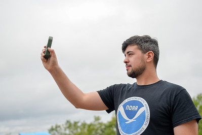 Raven Vasquez gathers current wind speeds and temperature using a pocket weather station prior to the launch.