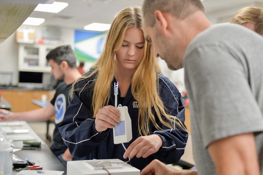 Laufey Jorgensdottir is guided by Paul Walter as she prepares an ozone sonde air pump.