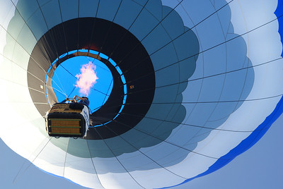 Blue hot air balloon with fire seen from below, at Great Forest Park Balloon Race in St. Louis, Missouri