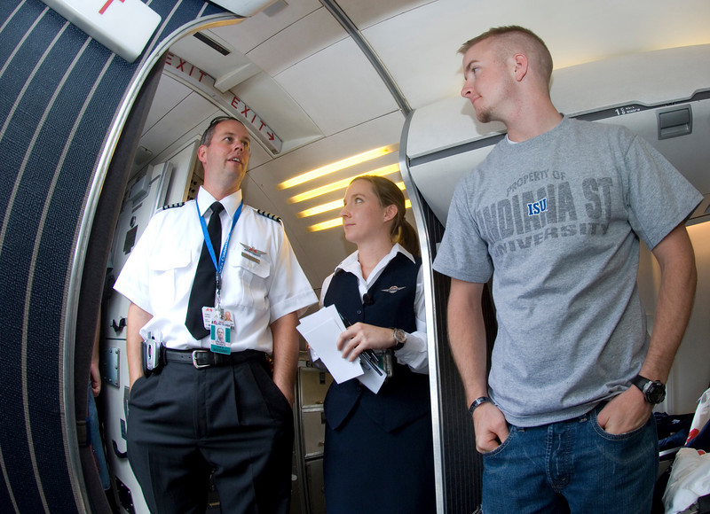 ASA employees Darrin Greubel and Rebecca Babb speak with ISU sophomore Michael Brunsman about the airline during a visit to Hulman Field.