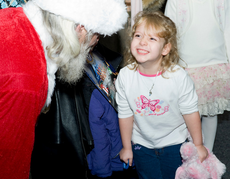 Cierra Orndorff, 4, and her stuffed dog Pinky tell Santa their wish list.